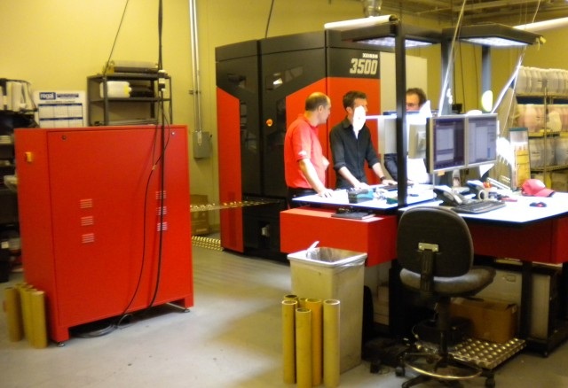 Operators confer at the controls of the Xeikon 3500 digital press.